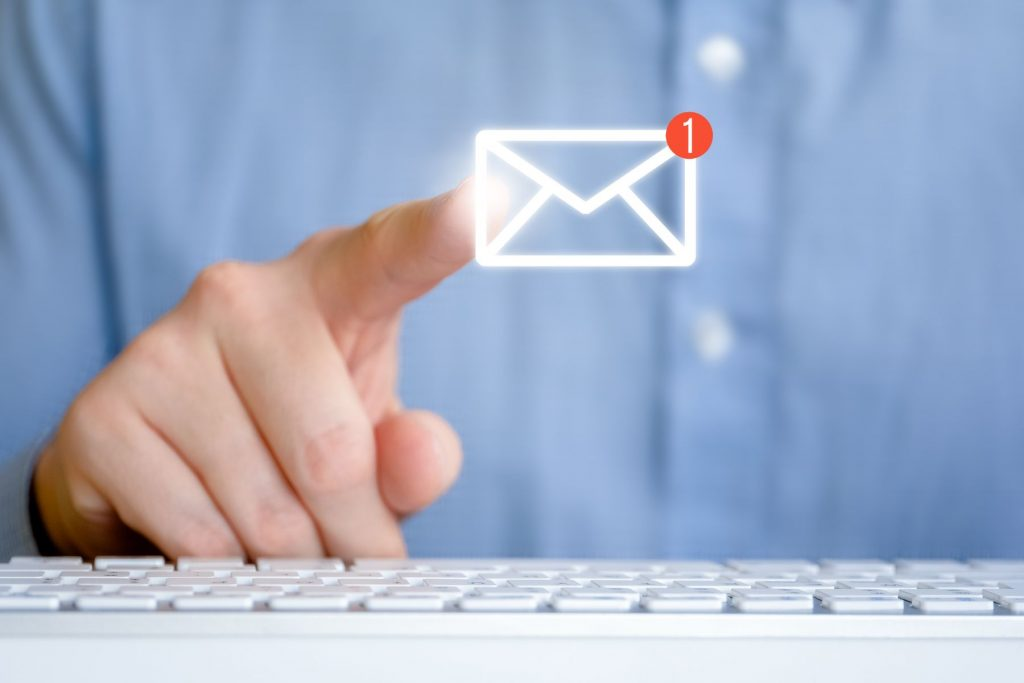 A man in a shirt in front of the keyboard. Abstract email icon with new message.