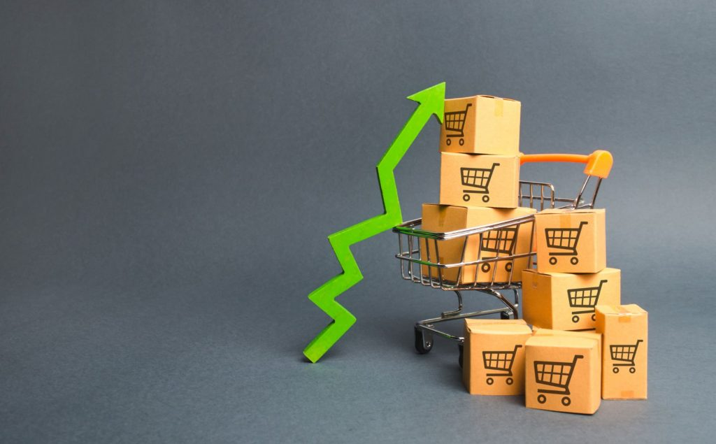 Shopping cart with cardboard boxes with a pattern of trading carts and a green up arrow. Increase the pace of sales, production of goods. Strategy for increasing revenue