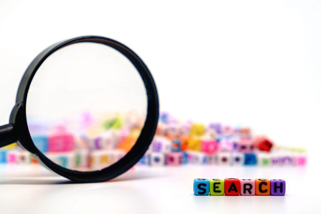 "Word ""SEARCH"" on the magnifying glass with alphabet letter beads background"